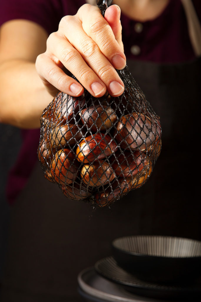chestnuts in mesh bag in hand